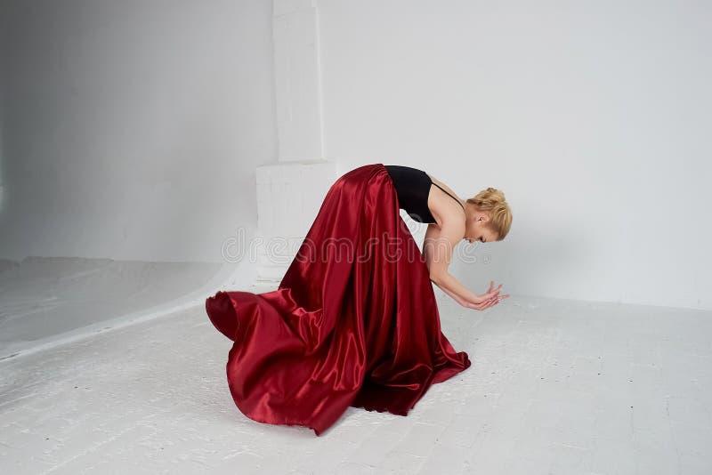 En gymnast i en m?rk ?verkant och en r?d siden- kjol F?rgen av passion, av agression tango Plast- kropp, airiness royaltyfria bilder