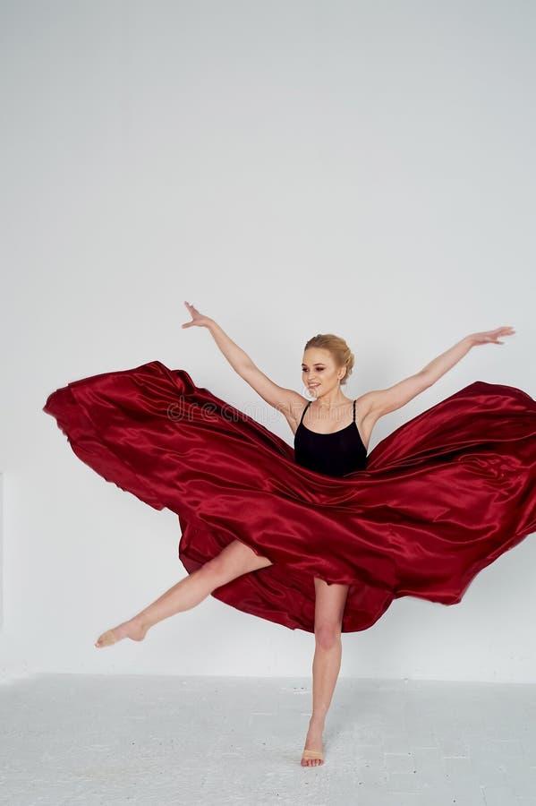 En gymnast i en m?rk ?verkant och en r?d siden- kjol F?rgen av passion, av agression tango Plast- kropp, airiness royaltyfria foton