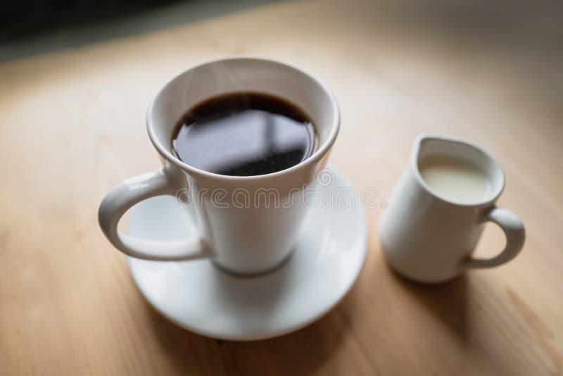 En gyttja svart kaffe och såser med en ledtråd intill en liten vit mjölkdryck fotografering för bildbyråer