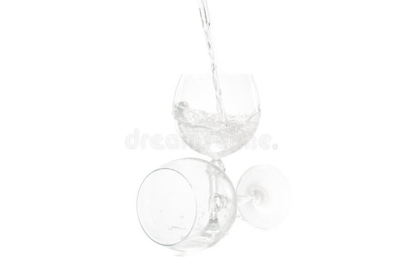 En hällande vattenfärgstänk i exponeringsglas på vit bakgrund royaltyfri fotografi