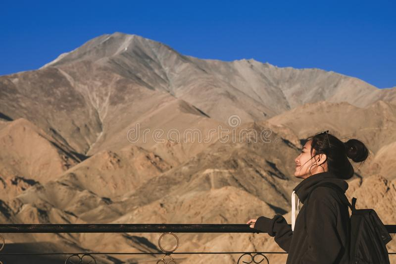 En härlig asiatisk kvinna för smiley som framme står av det Himalaya berget royaltyfri bild