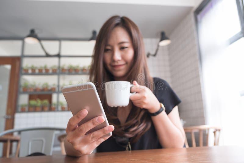 En härlig asiatisk kvinna med innehavet och att använda för smileyframsida den smarta telefonen, medan dricka varmt kaffe på trät royaltyfri foto
