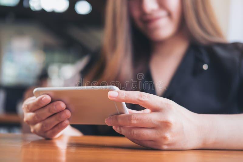 En härlig asiatisk kvinna med smileyframsidan som rymmer och använder som är horisontal, ilar telefonen till hållande ögonen på t fotografering för bildbyråer