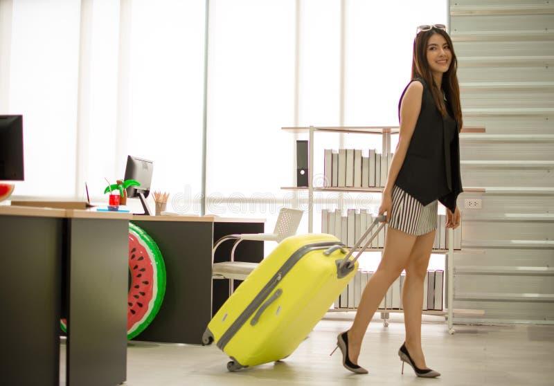En h?rlig asiatisk kvinna ska resa p? stranden efter fullf?ljande hennes arbete royaltyfri bild
