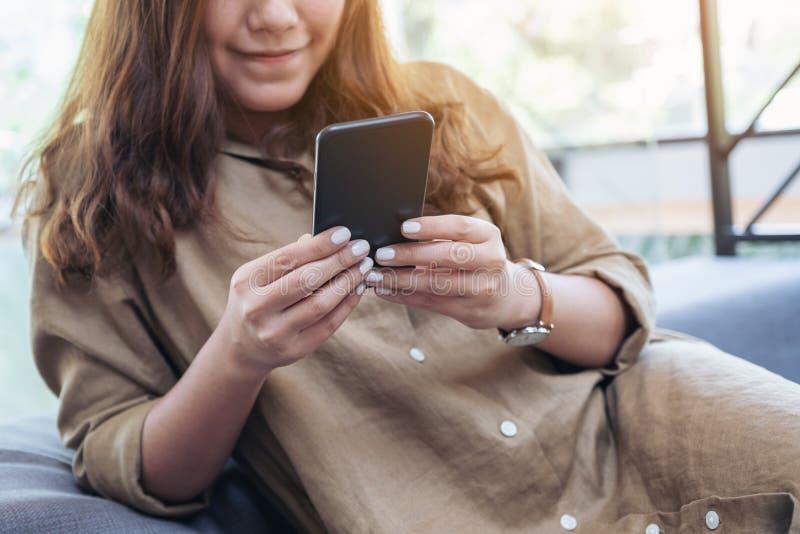 En härlig asiatisk kvinna som rymmer, använder och ser den smarta telefonen, medan sitta i vardagsrum arkivfoto