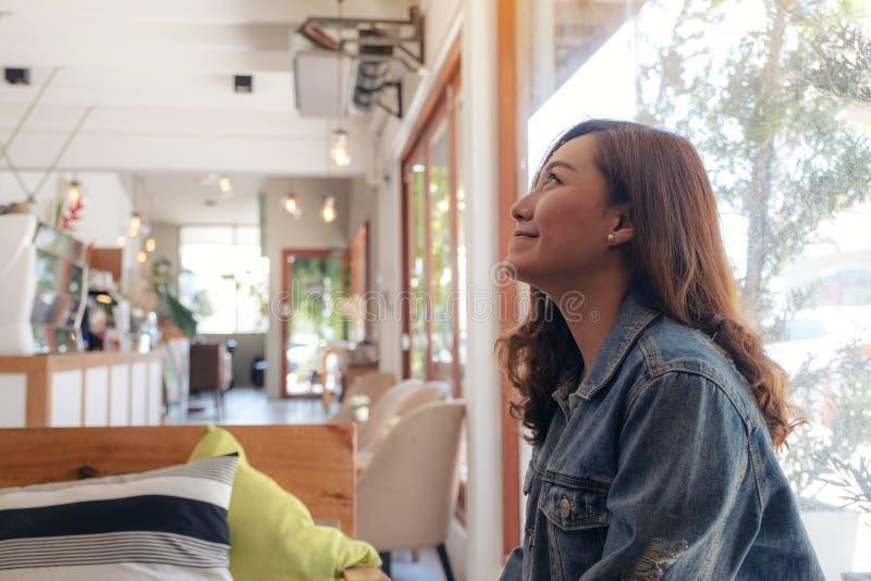 En härlig asiatisk kvinna som sitter i kafé royaltyfri fotografi