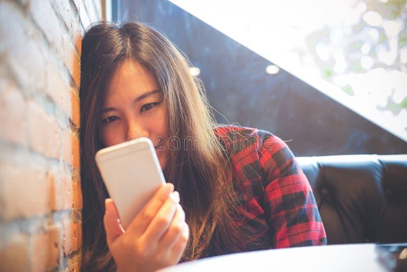 En härlig asiatisk kvinnabenägenhet för smiley på tegelstenväggen, medan genom att använda och se den smarta telefonen i modernt  arkivfoto