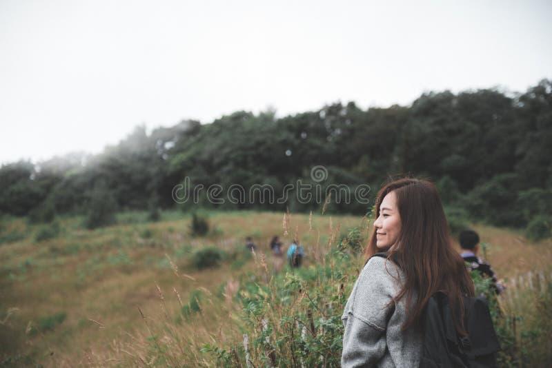 En härlig asiatisk kvinnaturist som går och trekking längs bergen i tropisk skog royaltyfri bild