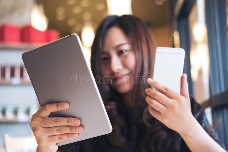 En härlig asiatisk PC för minnestavla för affärskvinna hållande och ilar telefonen, medan arbeta royaltyfri bild