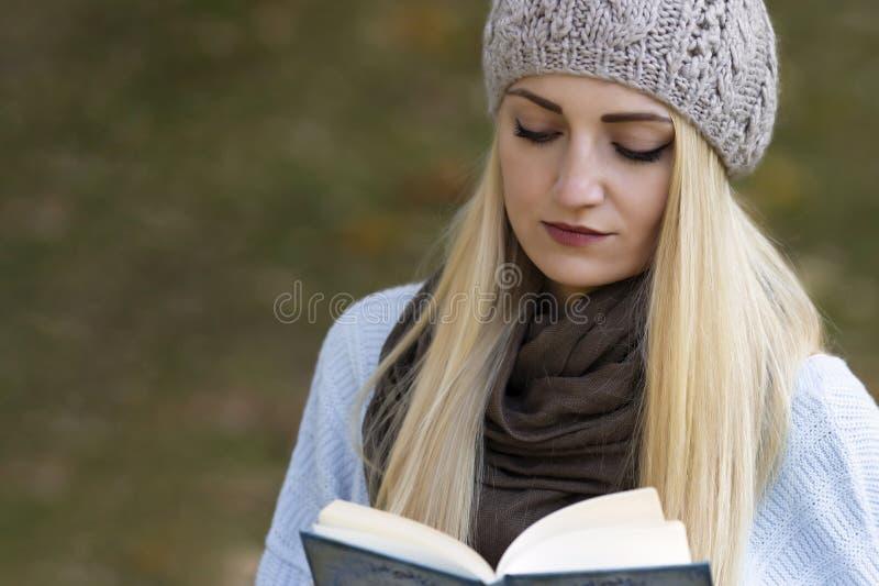 En härlig blond flicka med långt hår läser en bok royaltyfri foto