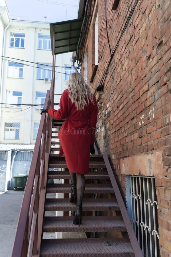 En härlig blond flicka som bär ett rött lag och handskar, klättrar en rostig metallstege nära en tegelstenvägg Mode som är kommer royaltyfri fotografi