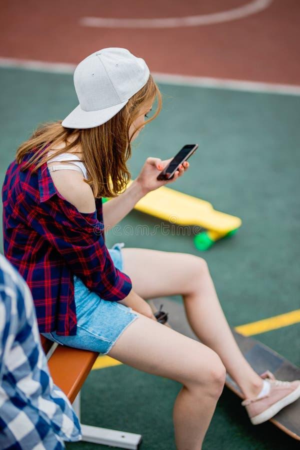 En härlig blond flicka som bär rutiga skjorta-, lock- och grov bomullstvillkortslutningar, sitter på sportfältet med en telefon i royaltyfria bilder