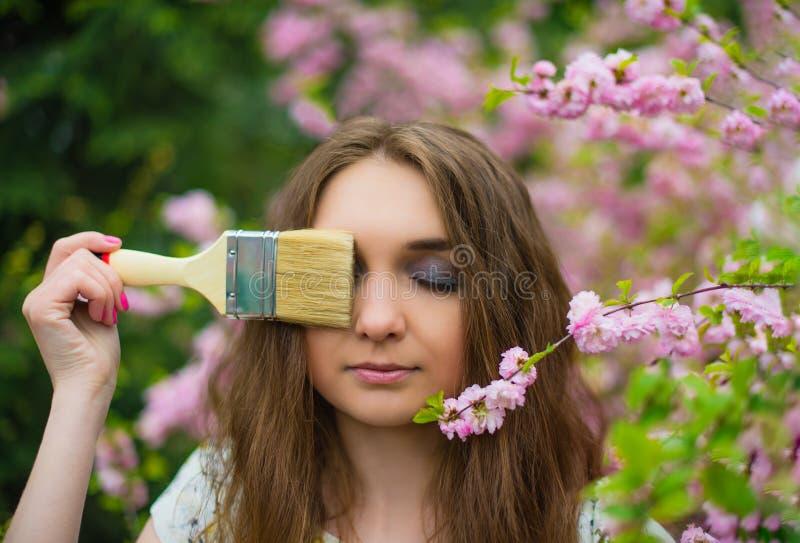 En härlig blond flicka står i trädgården av en blommande rosa Sakura med hennes stängda ögon och rymmer en målarfärgborste över e royaltyfri bild