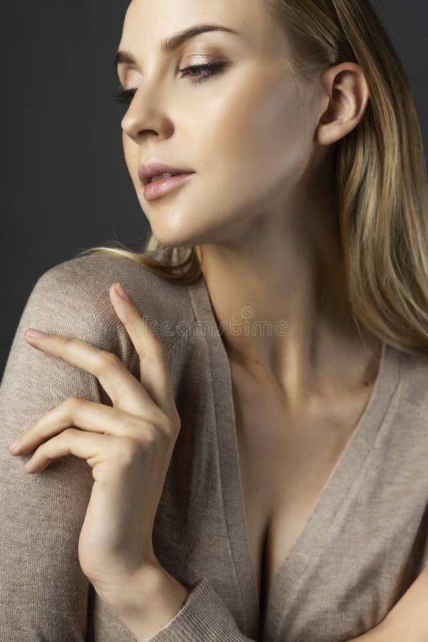 En härlig blond flickamodell som bär en stucken beige klänning, unb royaltyfria bilder