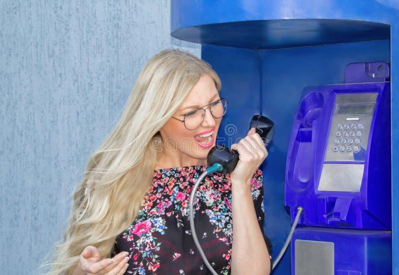 En härlig blond kvinna som wiaring exponeringsglas, rymmer en telefonmottagare i en payphone Känslomässigt rop in i telefonen arkivfoton
