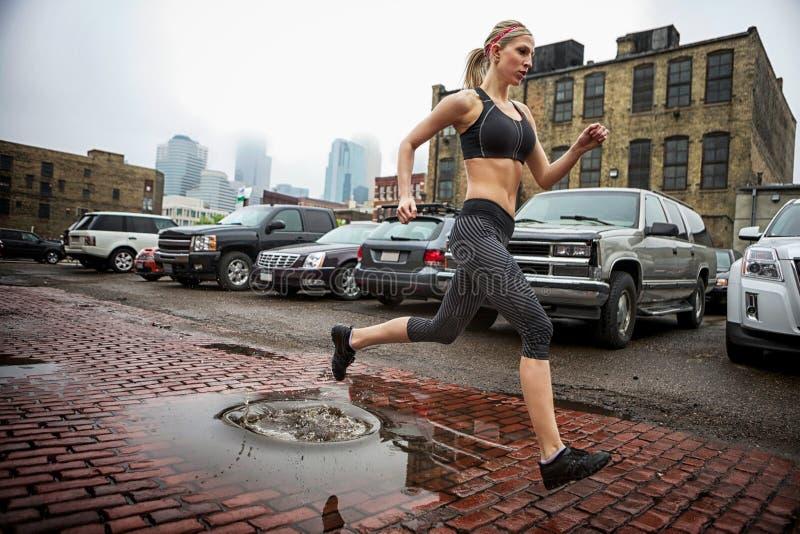 En härlig blond kvinnaspring på gatan royaltyfri fotografi