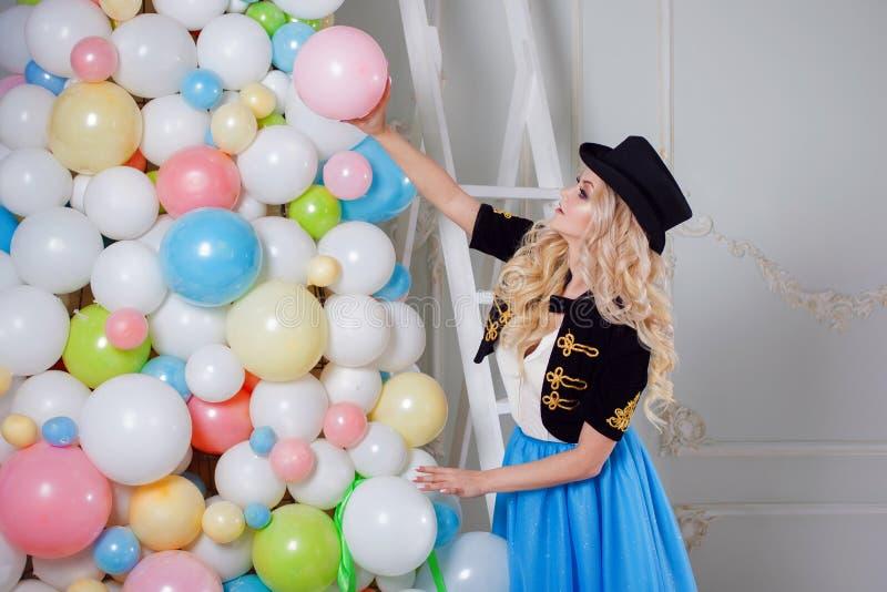 En härlig blondin i en karnevaldräkt dekorerar trädet av ballonger Den charmiga unga kvinnan i en curvy blått kringgår royaltyfri fotografi