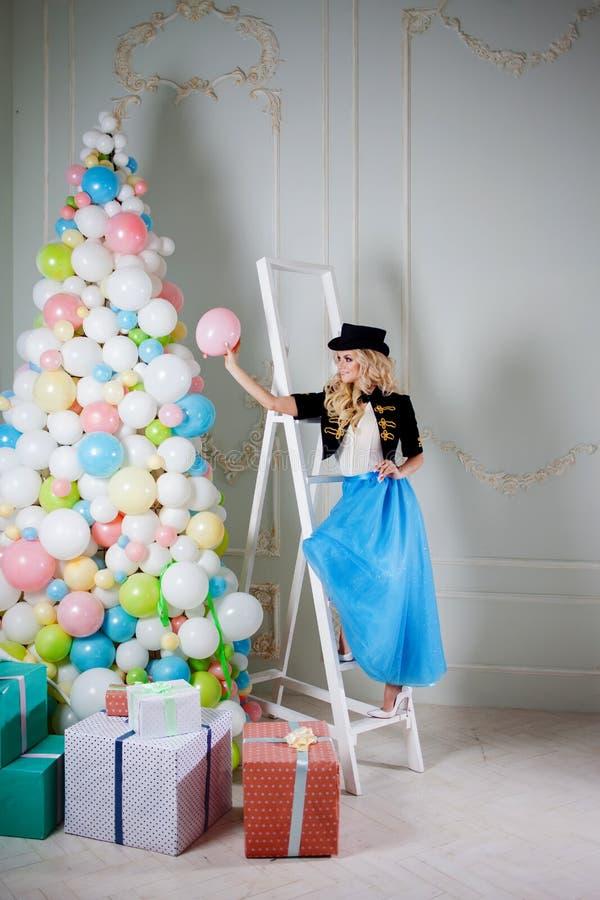 En härlig blondin i en karnevaldräkt dekorerar trädet av ballonger Den charmiga unga kvinnan i en curvy blått kringgår royaltyfria bilder