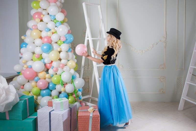 En härlig blondin i en karnevaldräkt dekorerar trädet av ballonger Den charmiga unga kvinnan i en curvy blått kringgår royaltyfria foton