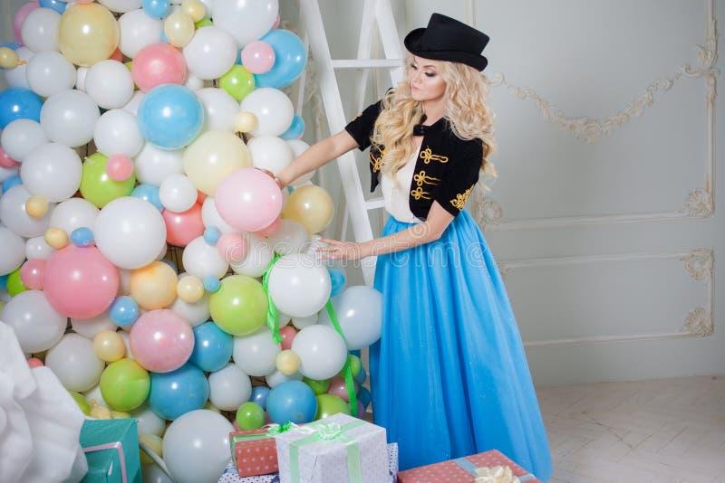 En härlig blondin i en karnevaldräkt dekorerar trädet av ballonger Den charmiga unga kvinnan i en curvy blått kringgår arkivbild