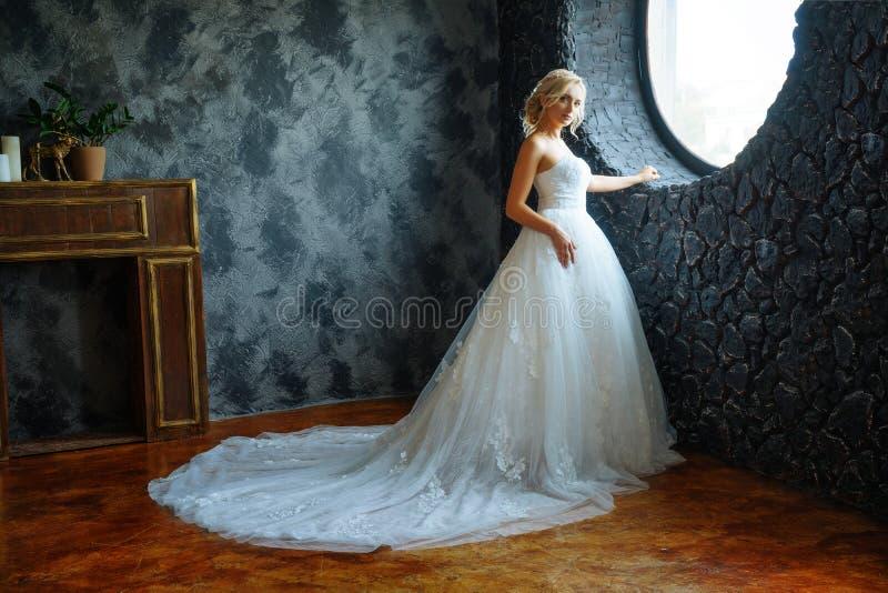 En härlig brud i en mycket härlig lång klänning med ett drev står vid fönstret royaltyfri bild