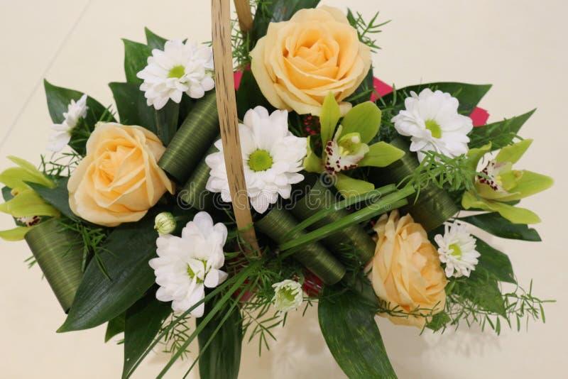 En härlig bukett av rosor, krysantemum och orkidér ska appellera till varje kvinna Hans kungliga doft ska er?vra varje arkivfoto
