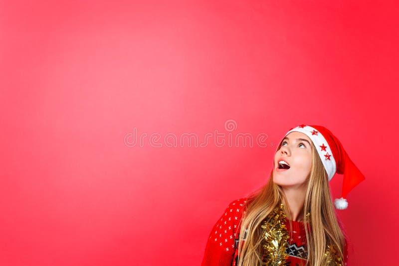 En härlig förvånad flicka i jultomten hatt, med glitter på hennes hals, blickar på det tomma kopieringsutrymmet på en röd bakgrun arkivfoton