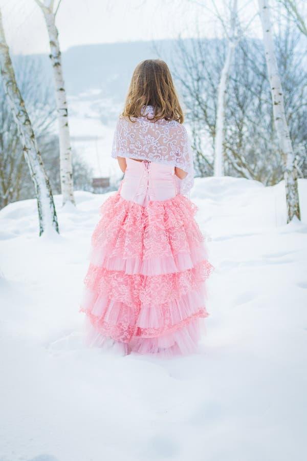 En härlig flicka går på en djupfryst skog som täckas med snö royaltyfri fotografi