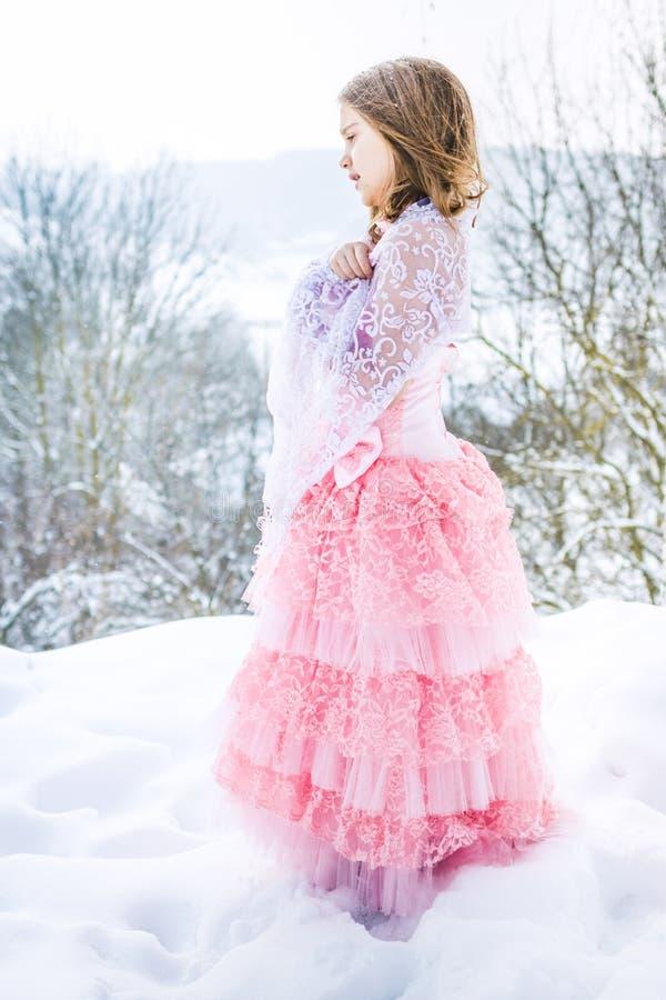 En härlig flicka går på en djupfryst skog som täckas med snö royaltyfri foto