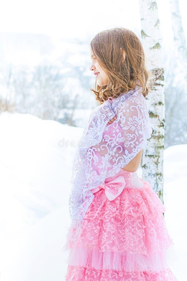En härlig flicka går på en djupfryst skog som täckas med snö royaltyfria bilder