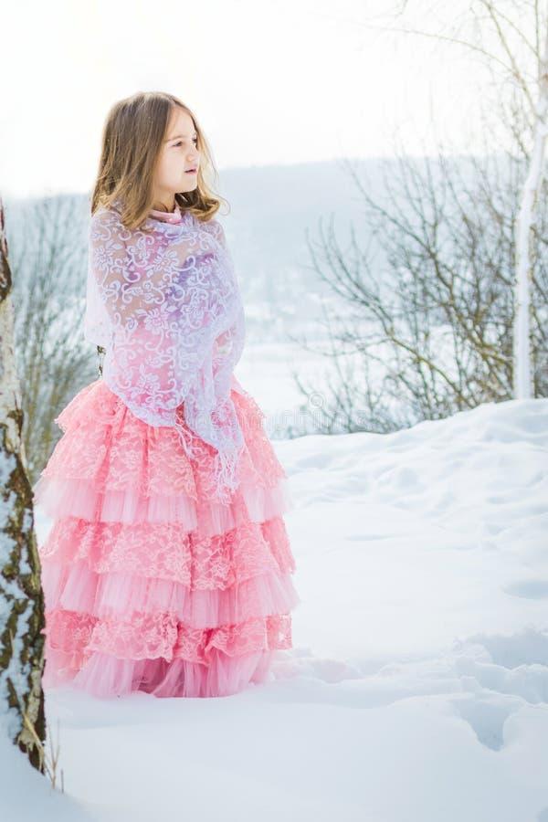 En härlig flicka går på en djupfryst skog som täckas med snö arkivfoton