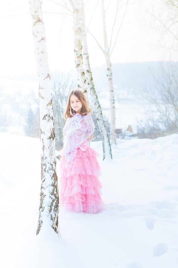 En härlig flicka går på en djupfryst skog som täckas med snö fotografering för bildbyråer