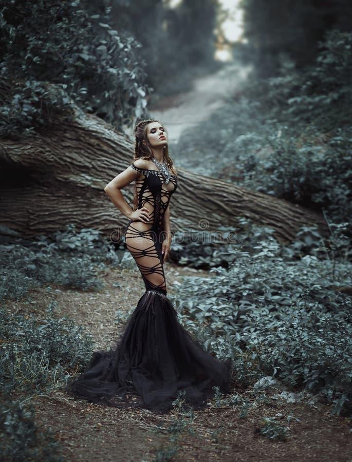 En härlig flicka i en ovanlig svart, sexig klänning royaltyfri fotografi