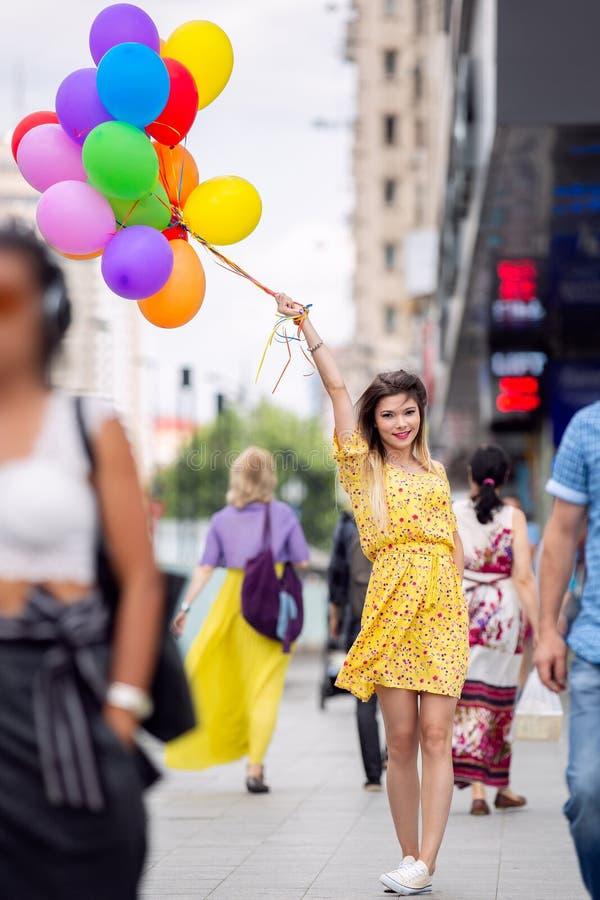 En härlig flicka i folkmassa med ballons i hand royaltyfri fotografi