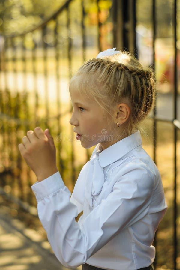 En härlig flicka i en vit blus utför ställningen i leken royaltyfria bilder
