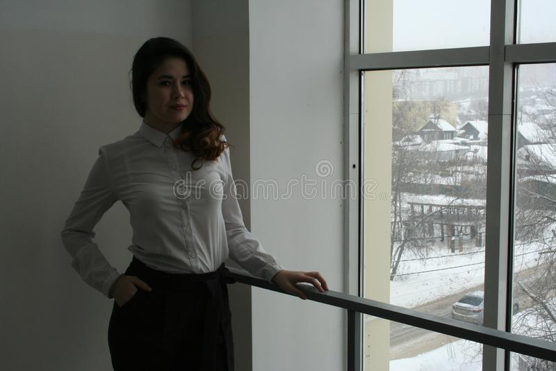 En härlig flicka i en vit blus väntar vid fönstret arkivbild