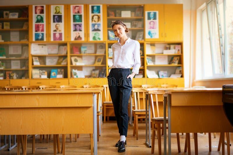 En härlig flicka i en vit skjorta står i klassrumet mellan skrivborden arkivfoto