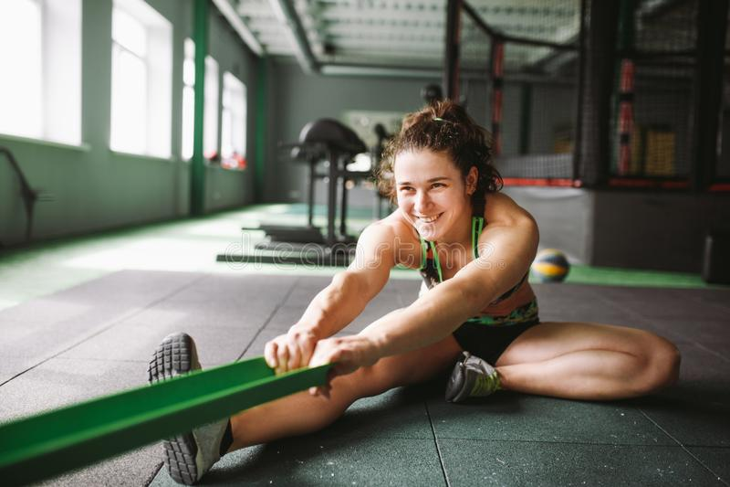 En härlig flicka med ett leende sträcker henne muskler, knådar, värmer upp, innan han utbildar i en skarv med en gummiband royaltyfri bild