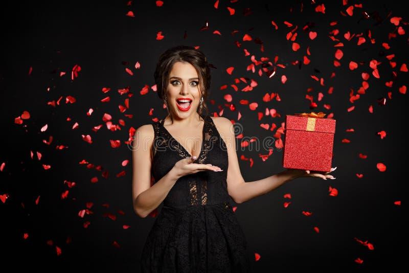 En härlig flicka med ett stort leende rymmer en gåva och är surpris royaltyfria bilder