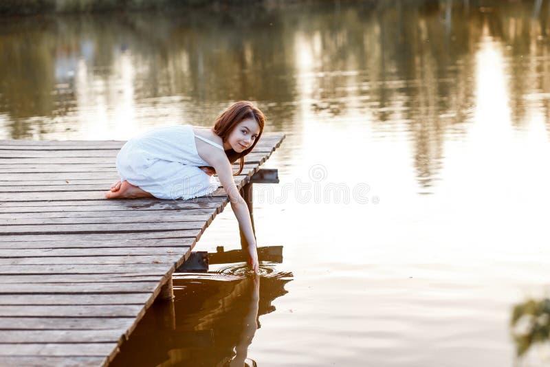 En härlig flicka med långt brunetthår och blåa ögon på pir nära vattnet på solnedgången arkivbilder