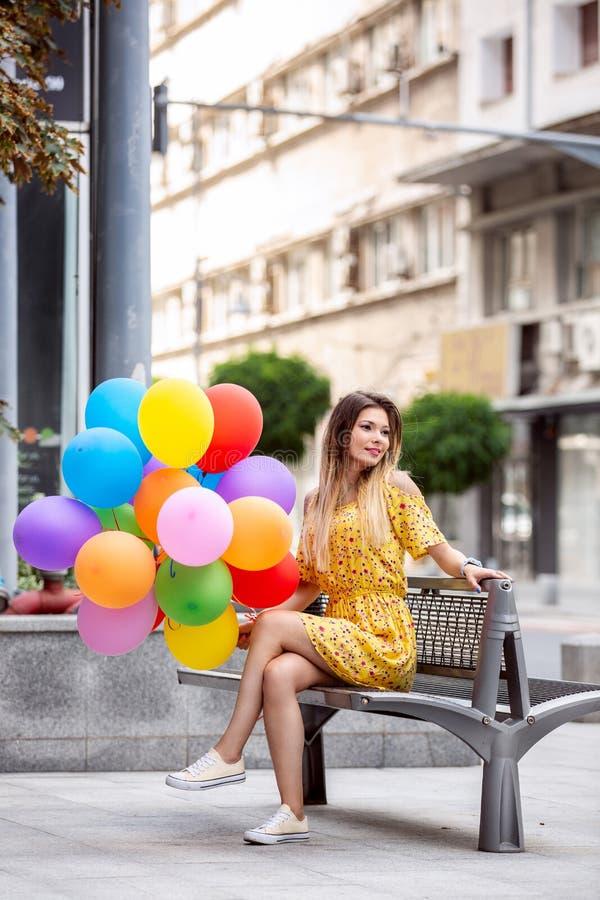 En härlig flicka sitter på en bank i staden med ballons i hand royaltyfri foto
