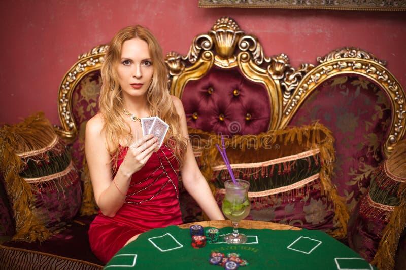 En härlig flicka sitter på en soffa som spelar poker på den gröna torkduken och, rymmer spela kort i hennes händer fotografering för bildbyråer