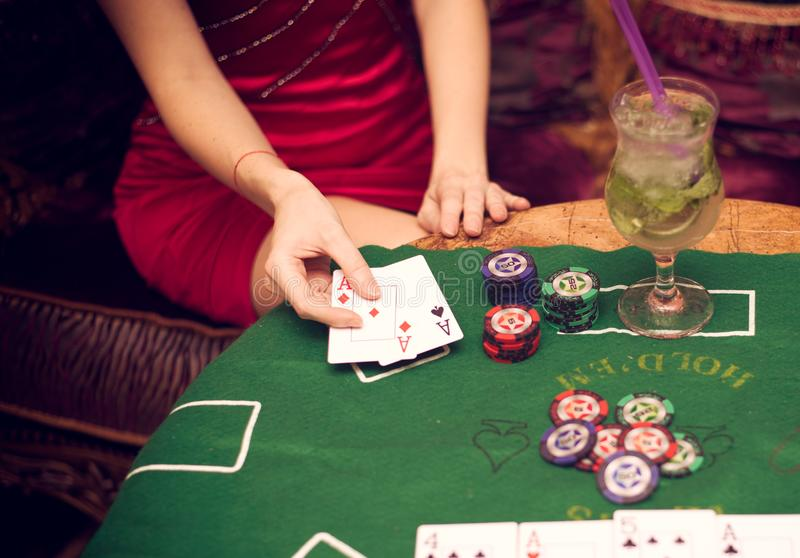 En härlig flicka sitter på en soffa som spelar poker på den gröna torkduken och, rymmer spela kort i hennes händer arkivbild