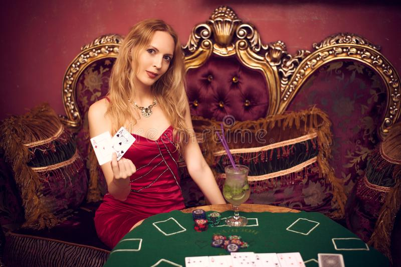 En härlig flicka sitter på en soffa som spelar poker på den gröna torkduken och, rymmer spela kort i hennes händer royaltyfri foto