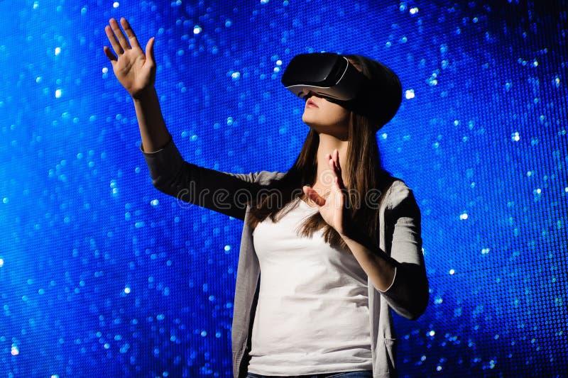 En härlig flicka som bär en virtuell verklighetapparat som står på bakgrunden av himlen arkivbild