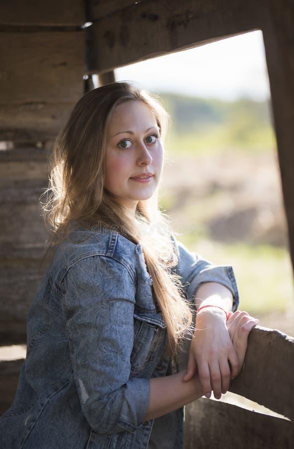En härlig flicka står nära ett träfönster royaltyfria foton