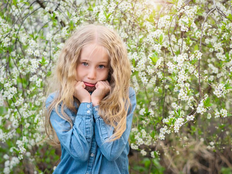 En härlig flicka stöttar hennes framsida med henne den körsbärsröda fruktträdgården för händer på våren arkivbild