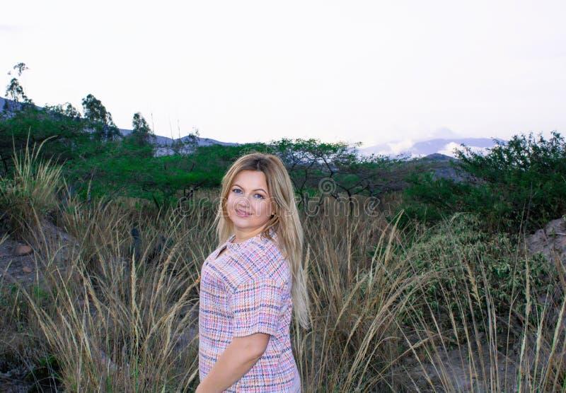 En härlig fyllig kvinna i en kort klänning Blondin Med ett härligt leende Utomhus på prärien och bergen i backgroen arkivbilder