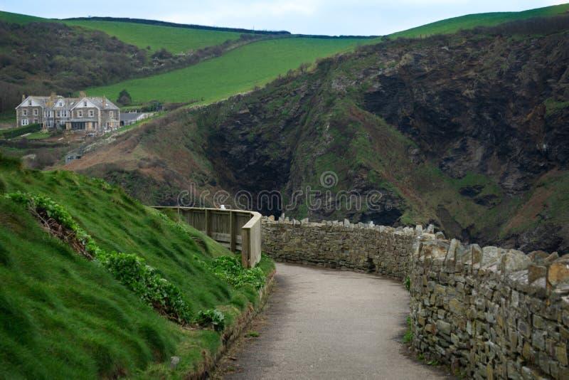 En härlig gammal stengångbana med berg och kullar som går in i port Isaac, Cornwall, England arkivfoto