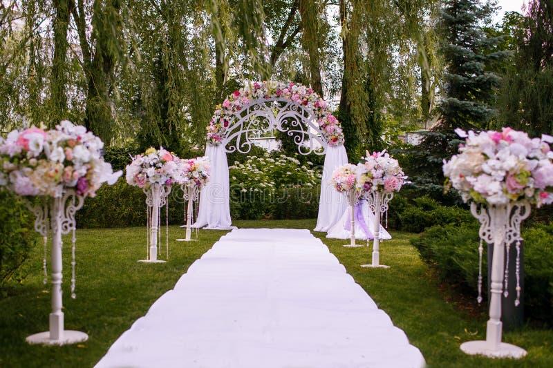 En härlig gifta sig båge som dekoreras med blommor i skogen, en vit bana, är klar för nygifta personerna royaltyfri bild